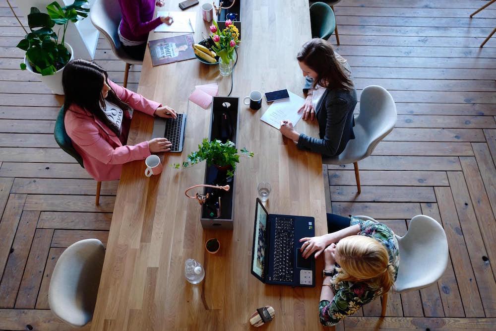 Drei Mitarbeiter sitzen in einem Büro. Zwei von ihnen schauen auf ihre Laptops und tätigen eine Mittagessensbestellung im Internet - Eine beliebte Alternative zur Kantine für die Mitarbeiterverpflegung