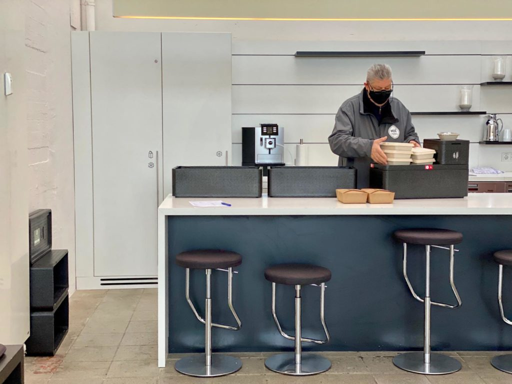 Ein Lieferfahrer liefert Mittagessen für die tägliche Verpflegung am Arbeitsplatz. Ein klassisches Szenario beim Lieferdienst für Mittagessen von mealmates.