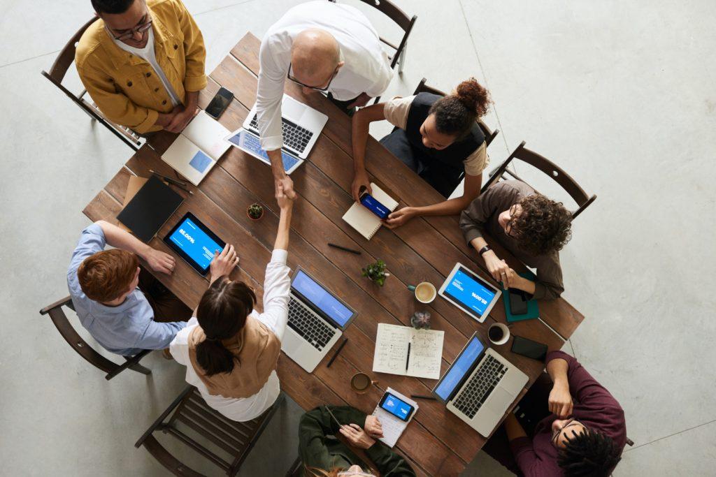 Mehrer Mitarbeiter sitzen am Tisch mit Laptop. Hier ist Mittagessen fürs Büro eine Alternative.