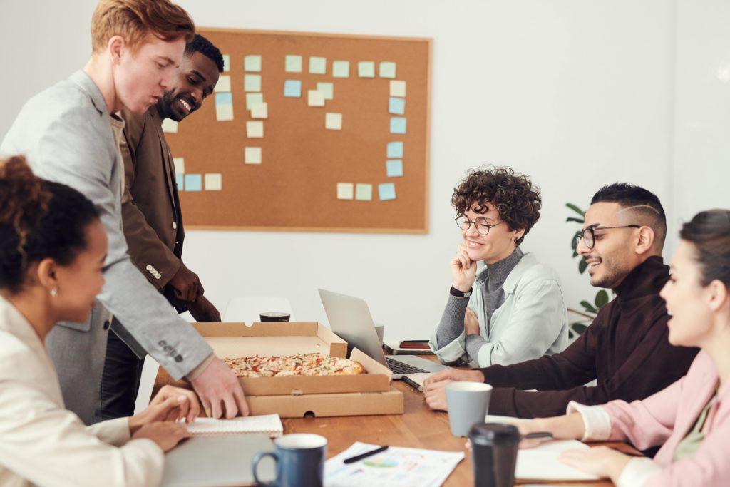 Office Catering: Kollegen sitzen zusammen am Arbeitsplatz und machen Mittagspause mit warmen Gerichten.