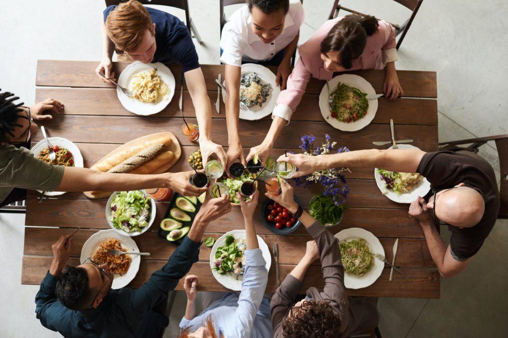 Ein Beispiel für die Gemeinschaftsverpflegung in Betrieben. Kollegen sitzen mit leckeren Gerichten zusammen am Tisch in der Mittagspause.