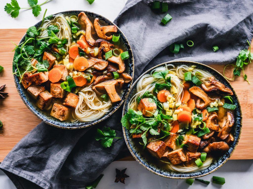 Zwei gesunde Bowls mit viel Gemüse, nudeln und Tofu. Gesunde Lieferdienste werden immer beliebter.