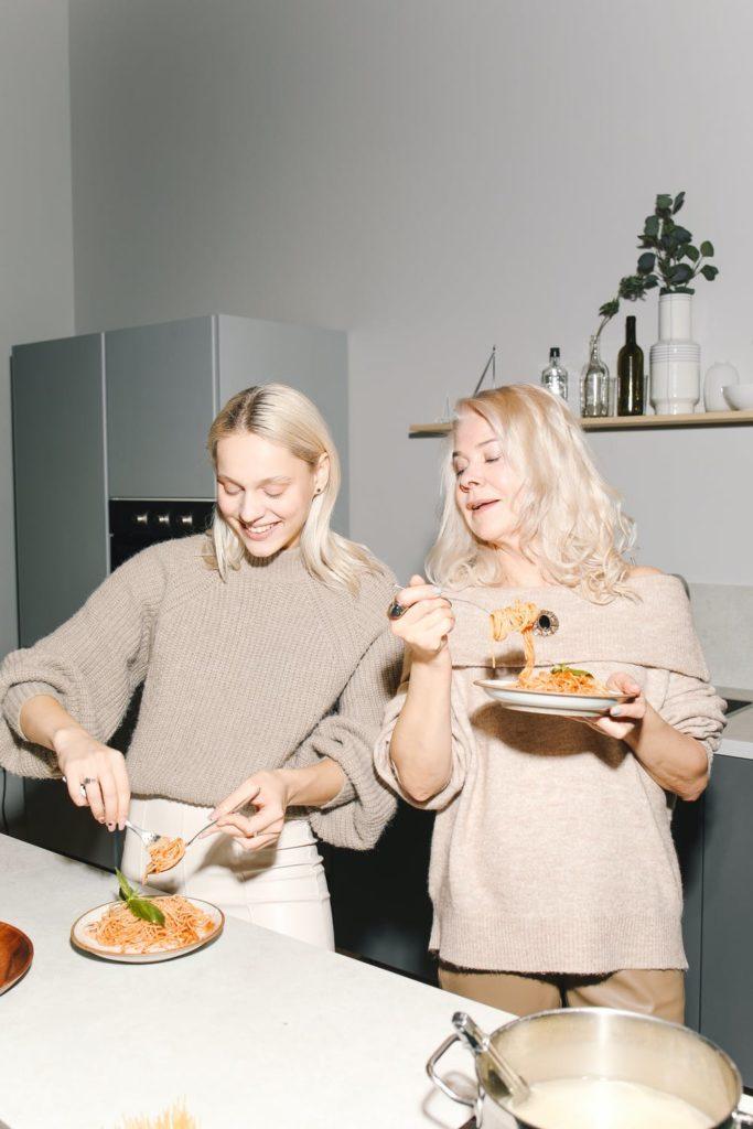 Bild von 2 Frauen mit einem Teller Pasta beim Teamessen in einer Büroküche.